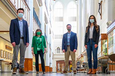 Four people physically distanced and masked pose for a photo in Jordan Hall of Science.