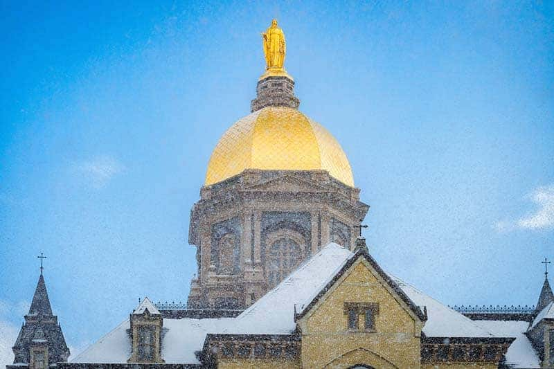 The Golden Dome shines as snow falls.