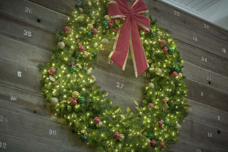 A decorated Christmas wreath with lights shining bright and a large, red bow attached on the top.