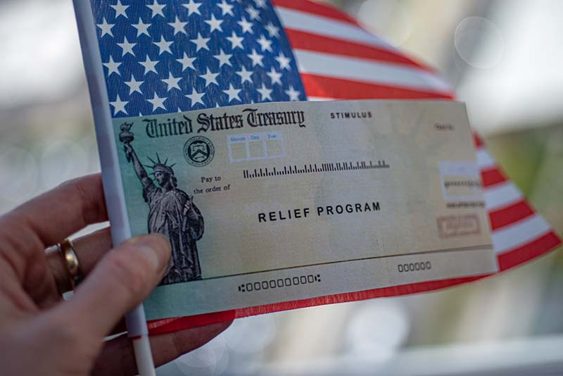 A US Treasury relief program check held in front of an American flag.