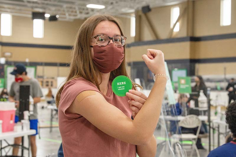 A masked student flexes her arm with a band-aid after being vaccinated, holding a HERE I got my vaccine sticker.