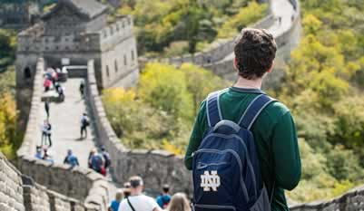 A young man wearing a blue Notre Dame backback is looking down the length of the Great Wall of China