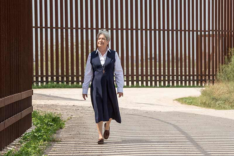 Sister Norma Pimentel, M.J. wearing a blue dress and walking next to a border wall