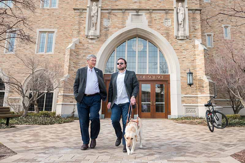 Two people walk on campus, one with a service dog.