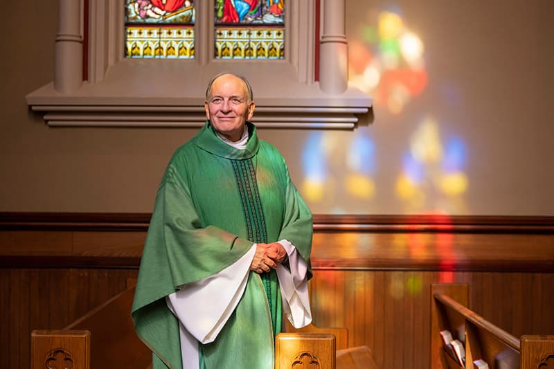 Fr. Rocca in green vestments looks off camera, with colorful light reflecting from the stained glass windows on the wall.