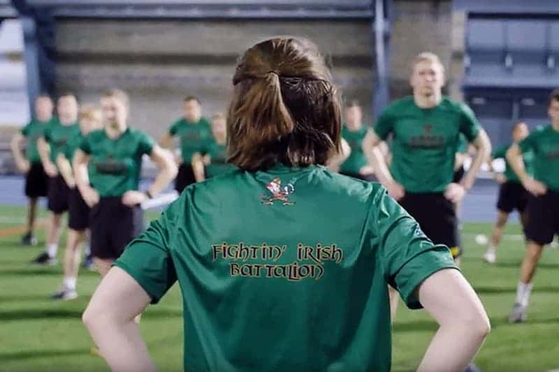 A female cadet wearing a green Fighting Irish Battalion shirt standing in front of a group of cadets with their hands on their hips.