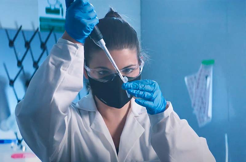 A masked, gloved and eye glasses-wearing woman does research in a lab.