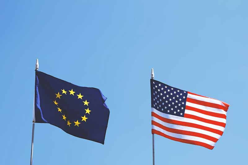 An American flag and European Union flag fly together.