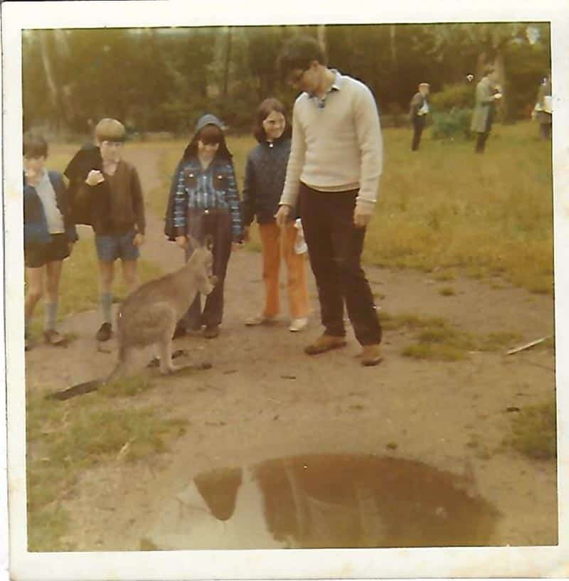 One adult and four kids stand around a kangaroo.