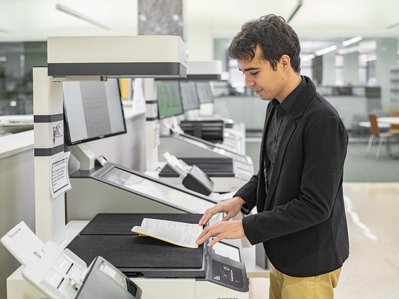 The student stands at a scanner in the library with the journal under the scanner.