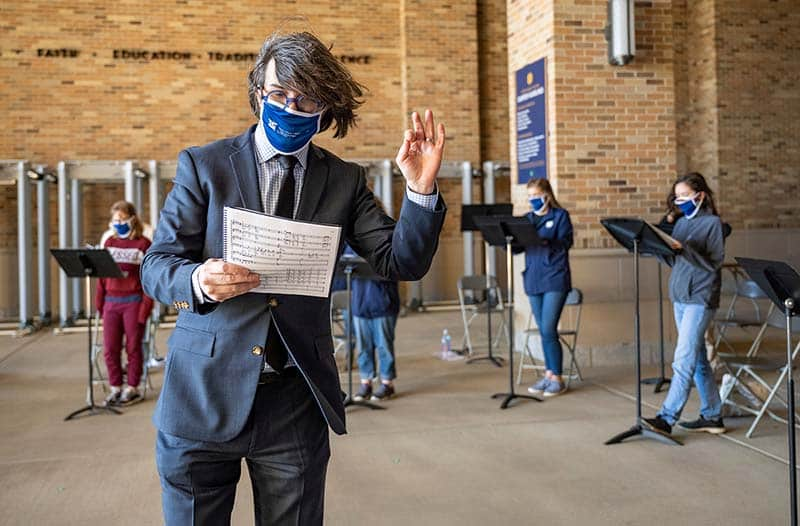 A masked man holding sheet music conducts a group of singers in the background.