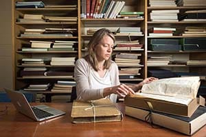 A female scholar sits at a desk with a pile of old books and a laptop.
