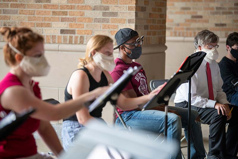 Close-up of students with masks on reading music sheets.