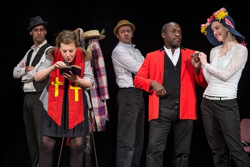 Students performing As You Like It on stage wearing a variety of colorful outfits