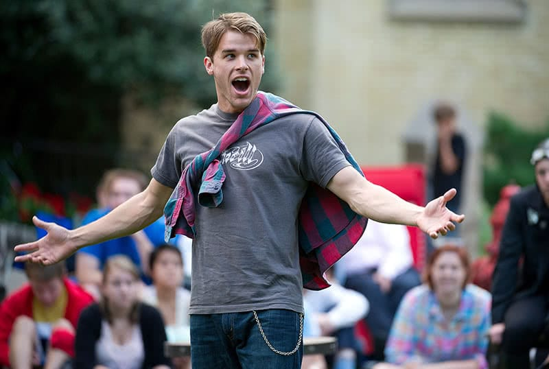 A young man performing at Notre Dame Shakespeare Festival while wearing a plaid shirt as a cape