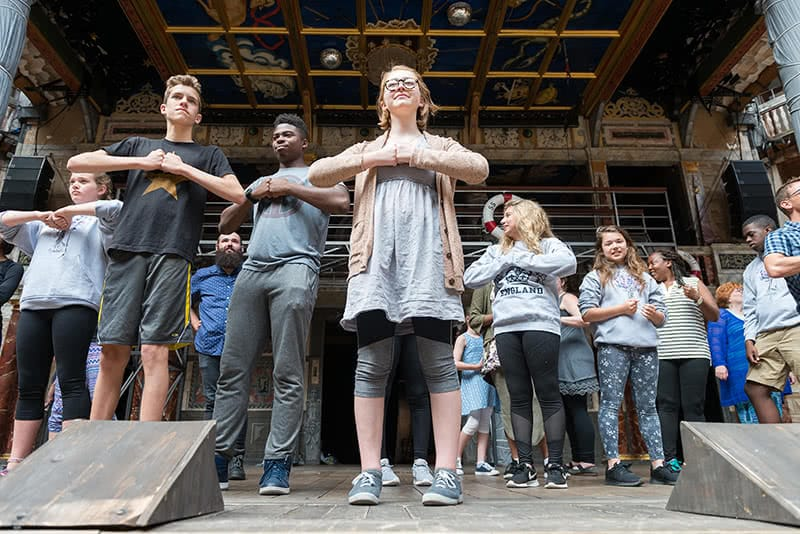 Over a dozen students from Robinson Community Learning Center in London standing on a stage with their fists touching in front of their chests